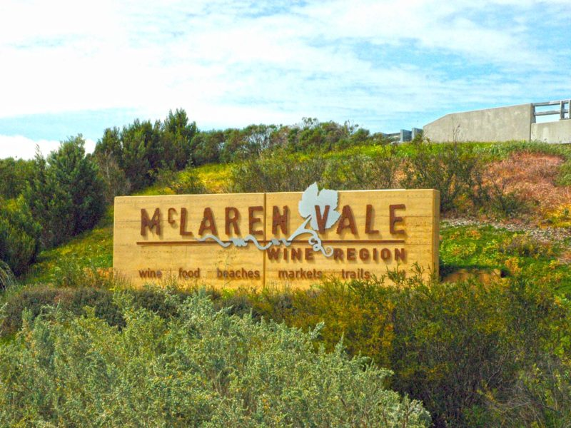 Sign for McLaren Vale wine region perched on a grassy hillside